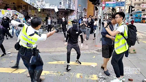 11일 오전 홍콩 사이완호에서 오전 경찰이 시위대를 향해 실탄을 발사하는 모습. 총알에 맞은 21세 학생은 여전히 위독한 상태다. [로이터=연합]