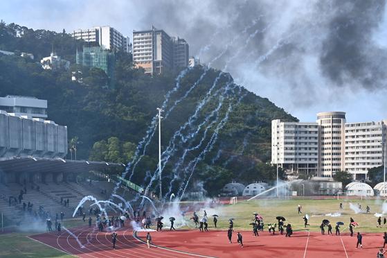 지난 12일 홍콩 중문대 캠퍼스에서 홍콩 경찰이 대학생 시위대를 향해 최루탄을 쏘고 있다. [AFP=연합뉴스]