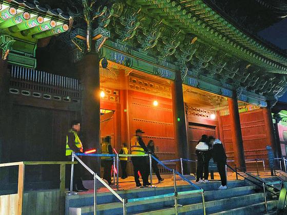 지난 6일 정부의 노인 일자리 사업으로 고용된 안내 요원(형광색 조끼)들이 서울 시내 한 고궁의 야간개장 행사에서 관람객의 입장권을 검사하고 있다. 이들은 4~11월 임시로 일한다. 허정원 기자
