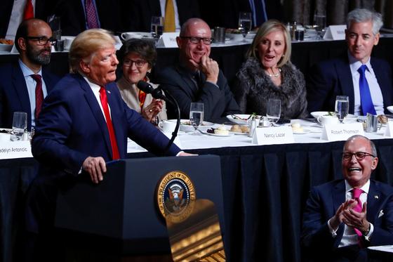 도널드 트럼프 미국 대통령이 12일(현지시간) 뉴욕경제클럽에서 기업인들을 대상으로 연설하고 있다. 트럼프 대통령 농담에 래리 커들로(오른쪽) 백악관 국가경제위원장이 웃음을 터뜨렸다. [로이터=연합뉴스]