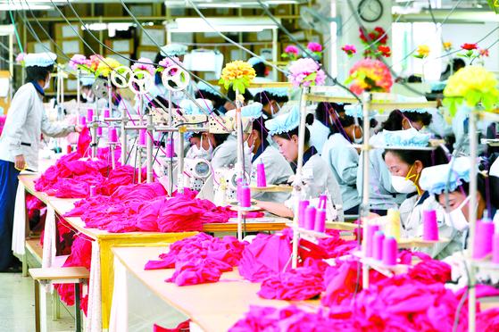 한국 기업 철수 전인 2013년 9월 개성공단 내 한국 의류업체에서 일하는 북한 근로자들. 남북 경협 논의에서 민간 목소리가 반영되지 않아 성과를 내지 못한다는 지적이 나온다. [중앙포토]