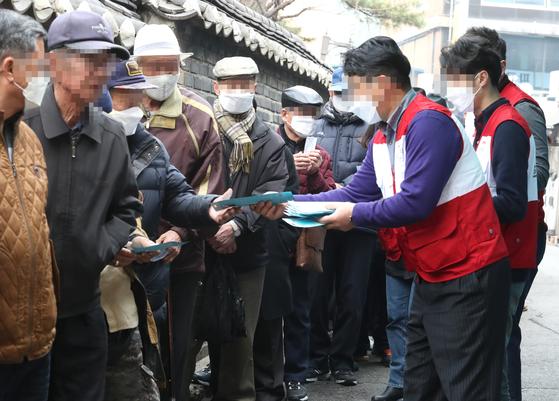 지난 3월 서울 탑골공원 인근에서 한 시민단체 회원들이 노인들에게 미세먼지 마스크를 나눠주고 있다. [연합뉴스]