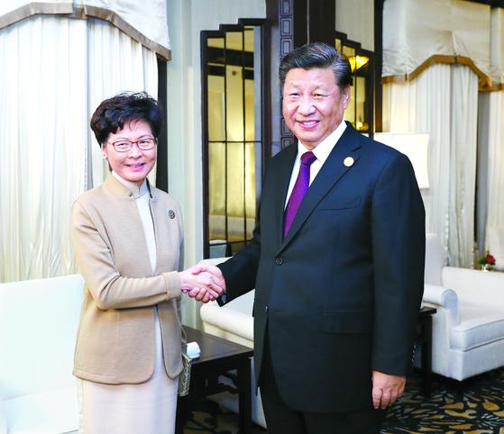시진핑 중국 국가주석(오른쪽)이 4일(현지시간) 상하이에서 캐리 람 홍콩 행정장관을 만나 악수하고 있다. 시 주석은 경질설이 나돌던 람 장관에 대한 재신임 의사를 밝혔다. [연합뉴스]