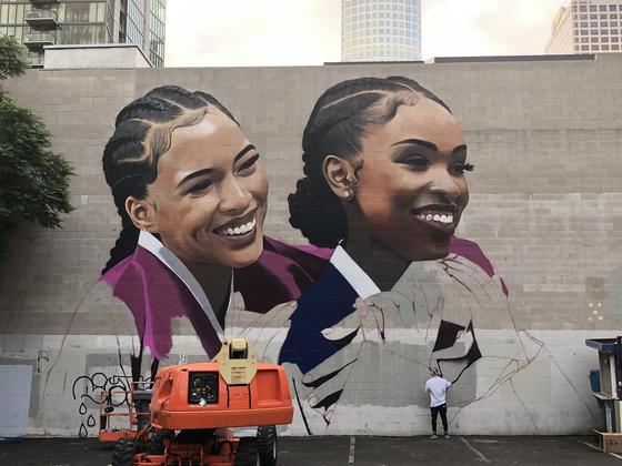 지난 10월 미국 로스엔젤레스 현지에서 심찬양 작가가 LG유플러스와 애플 아이폰11 프로 공동 광고를 위해 다운타운 뮤직센터의 가로 30미터, 세로 15미터 규모의 대형 벽면에 한복을 입은 외국인 여성을 그리고 있는 장면. [사진 LG유플러스]