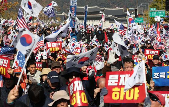 9일 오후 서울 광화문 교보빌딩 앞에서 문재인하야범국민투쟁본부 주최로 열린 대한민국 바로 세우기 국민대회에서 참가자들이 구호를 외치며 태극기와 손팻말을 흔들고 있다. [연합뉴스]