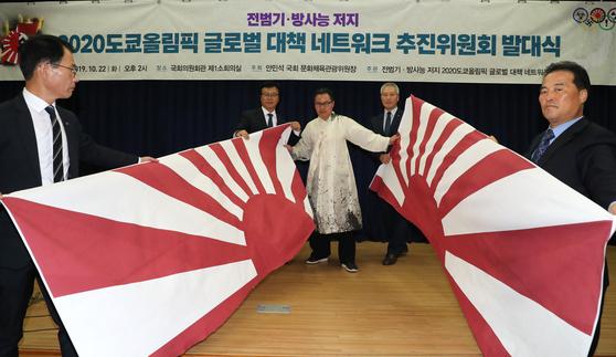 지난달 22일 오후 국회 의원회관에서 열린 전범기·방사능 저지 '2020도쿄올림픽 글로벌 대책 네트워크 추진위원회 발대식'에서 캘리아티스트 권도경 작가가 일본 전범기인 욱일기를 찢는 퍼포먼스를 하고 있다.[연합뉴스]
