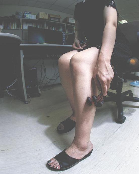 하지정맥류로 다리가 불편한 한 여성이 사무실에서 다리를 주무르고 있다. [중앙포토]