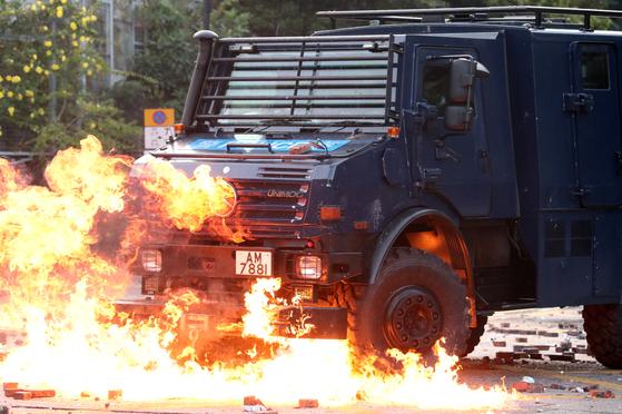 17일 시위대가 던진 화염병에 홍콩 경찰 차량이 불타고 있다. [로이터=연합]