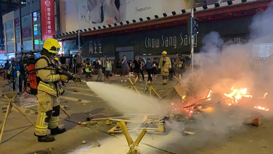 지난 15일 밤 홍콩 구룡반도의 시위 빈발지역인 몽콕 거리에서 시위대가 화염병으로 지른 화재를 소방대가 출동해 진화하고 있다. 신경진 기자