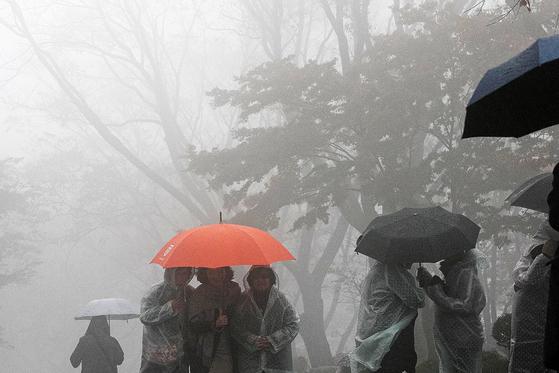 수도권과 강원북부 지역을 중심으로 비가 내린 지난 15일 서울 중구 남산에서 관광객들이 우산을 쓰고 발걸음을 재촉하고 있다. [뉴스1]