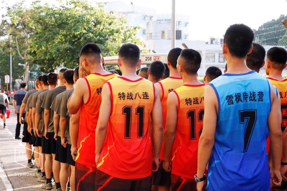 홍콩 주둔 인민해방군이 16일 오후 홍콩 침례대 부근 도로의 장애물 제거 작업에 나서기에 앞서 도열해 있다. 청소에 동원된 60여명의 병사 중 일부는 오렌지색 '특전8연대' 조끼를 입고 있다. [사진=입장신문]