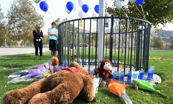 14일(현지시간) 총격 사건이 발생한 미국 로스앤젤레스 북서쪽 도시 샌타클라리타의 소거스 고등학교에서 시민들이 희생자들을 추모하고 있다. 이날 사고로 2명이 숨지고 3명이 다쳤다. 용의자는 치료 도중 숨졌다. [연합뉴스]