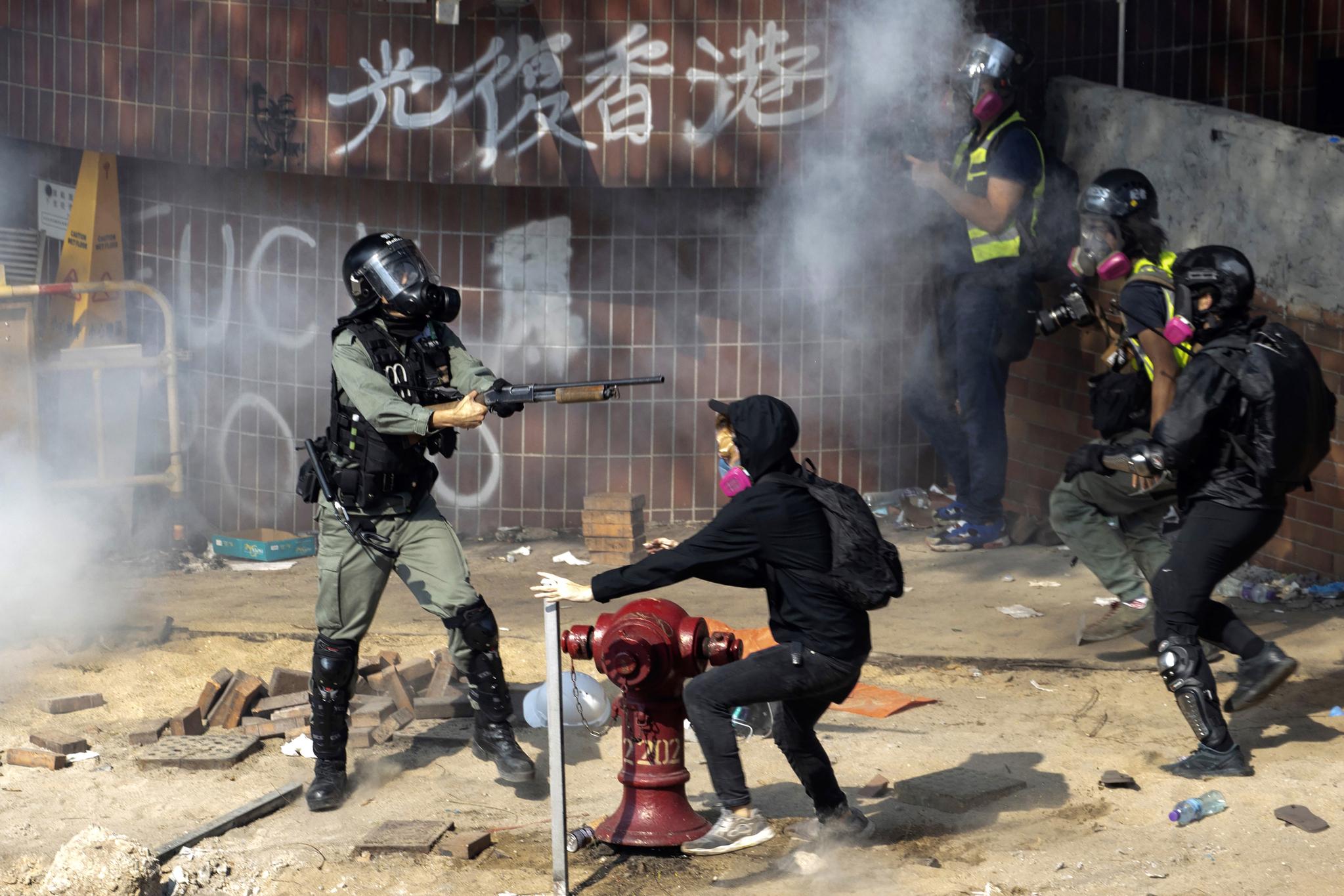 18일(현지시간) 홍콩 이공대 인근에서 경찰이 총을 겨누자 놀란 시위대와 취재진이 흩어지고 있다. [AP=연합뉴스]