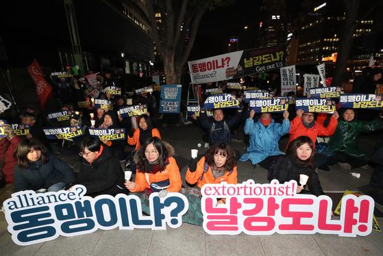 18일 오후 서울 종로구 주한미국대사관 앞에서 민중당 주최로 열린 방위비분담금 3차 협상 대응 긴급 촛불 집회에서 참석자들이 방위비분담금 삭감을 주장하고 있다. [연합뉴스]