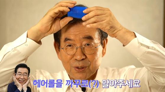 박원순 서울시장이 지난 15일 개인 유튜브 채널 '박원순TV'에서 과거와 달리 머리숱이 풍성해 보이는 비밀을 공개하고 있다. 그는 제일 먼저 헤어롤로 머리숱을 한껏 띄어준다고 설명했다.['박원순TV' 유튜브 캡처]