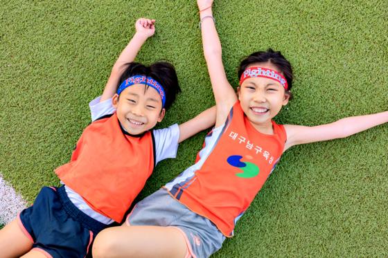 달리기 후 운동장 잔디 위에 누운 김성군(왼쪽)·하진 남매.