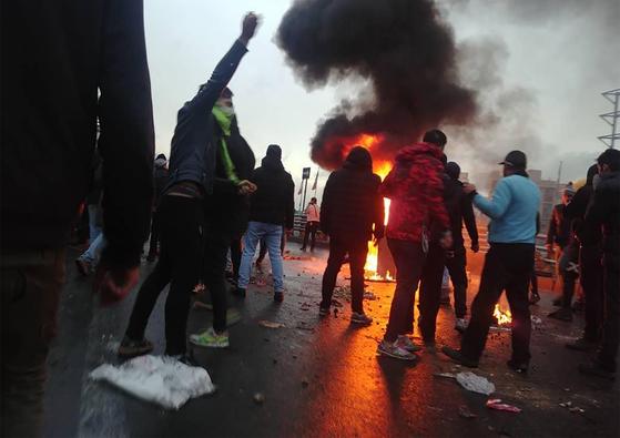 정부의 휘발유 보조금 삭감 방침에 반발한 이란 시위대가 16일 수도 테헤란에서 거리에서 불을 지르고 시위를 벌이고 있다.[AFP=연합뉴스]