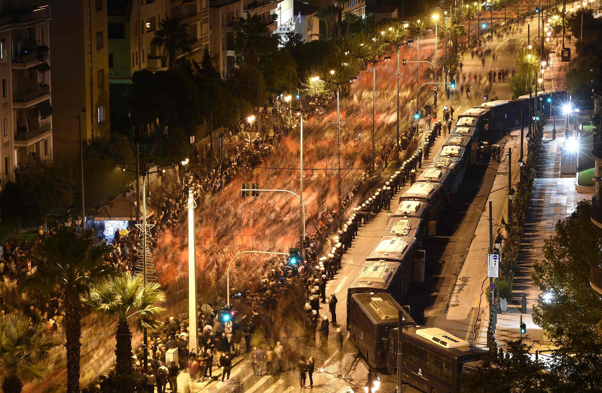 17일(현지시간) 그리스 아테네에서 1973년 군사 독재정권에 항거했던 학생봉기 46주년을 기념하는 연례 대규모 시위가 열렸다. 이날 시위에 참석한 시민들이 경찰 차벽과 병력 옆으로 행진하고 있다. [AFP=연합뉴스]