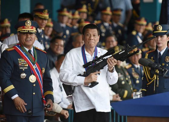 로드리고 두테르테(가운데) 필리핀 대통령이 지난해 4월 마닐라에서 열린 경찰총장 이임식에 참석해 기관총을 들어보이고 있다. [로이터=연합뉴스]