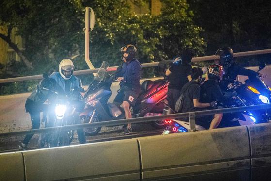 18일 오후 해가 지면서 홍콩 이공대에 남아 있던 학생 일부가 경찰의 체포를 피해 육교에 걸어놓은 밧줄을 타고 탈출했다. 탈출에 성공한 학생이 밖에서 기다리던 오토바이를 타고있다. [AFP=연합]