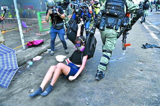홍콩 경찰이 18일 이공대 주변의 시위현장에서 한 여성 시위대를 붙잡아 끌고 가고 있다. 경찰은 시위대의 마지막 보루인 이공대를 포위해 진압 작전에 들어갔다. [AFP=연합뉴스]
