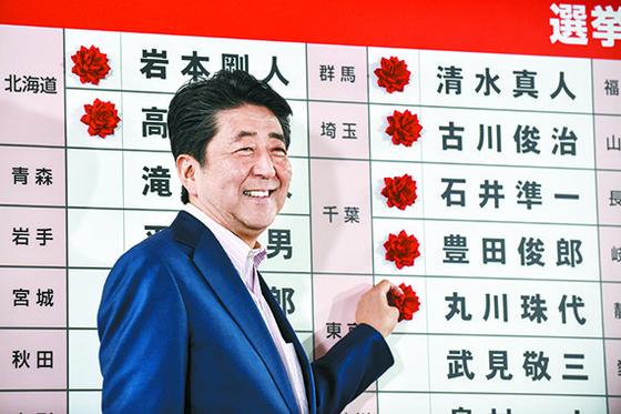 지난 7월 21일 실시된 일본 참의원 선거 직후 아베 신조 총리가 도쿄의 자민당 본부를 찾아 밝은 표정으로 당선이 확실시되는 후보 이름 앞에 장미꽃을 붙이고 있다. [AFP=연합뉴스]