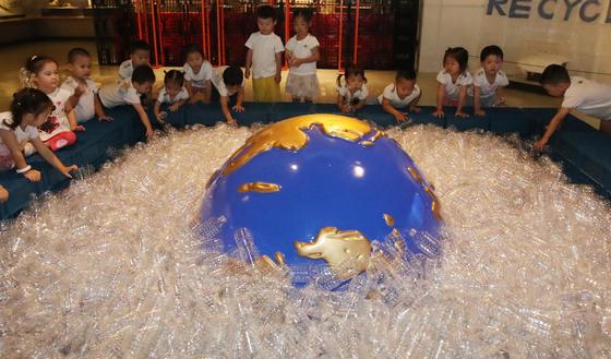 지난 8월 21일 부산 동래구 해양자연사박물관 특별전시실에서 '플라스틱 이제 그만(No More Plastic)' 기획전이 열려 관람 온 어린이들이 일회용 페트병에 파묻힌 지구를 형상화한 설치 작품을 살펴보고 있다. 플라스틱 사용량 감축과 함께 진행되는 재활용 과정에서, PET는 최상급의 재활용 원료로 꼽힌다. [중앙포토]