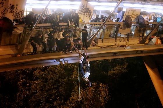 학생들이 18일 밤 경찰을 피해 홍콩이공대 건물에서 로프를 이용해 외부로 탈출하고 있다. 이들은 교내 건물과 인접한 고속도로로 탈출했다.[로이터=연합뉴스]