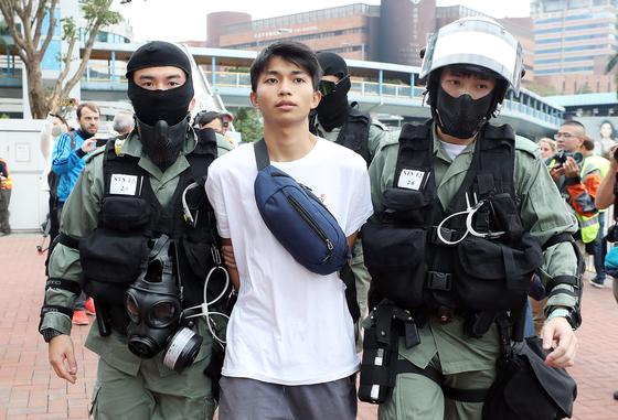 19일 오후 홍콩 이공대학교에서 투항한 시위 참여 학생이 경찰과 함께 밖으로 나오고 있다.[뉴스1]