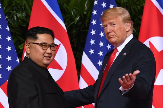 지난해 6월 싱가포르에서 정상회담을 한 도널드 트럼프 미국 대통령과 김정은 북한 국무위원장. 트럼프 행정부를 비판한 익명의 미 행정부 고위 관리는 19일(현지시간) 발간한 책 '경고'에서 트럼프 대통령이 김정은 위원장에게 매료됐다고 썼다. [AFP=연합뉴스]