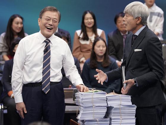 문재인 대통령이 19일 오후 서울 상암동 MBC에서 '국민이 묻는다, 2019 국민과의 대화' 종료 후 시간 관계상 받지 못한 질문지를 전달받고 있다. [연합뉴스]