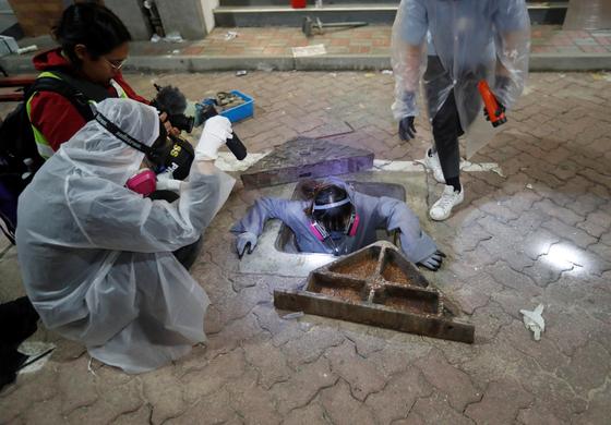 홍콩 경찰의 '봉쇄'작전에 몰린 학생들이 19일 홍콩 이공대 내 하수구를 통해탈출구를 찾고 있다. [로이터=연합뉴스].