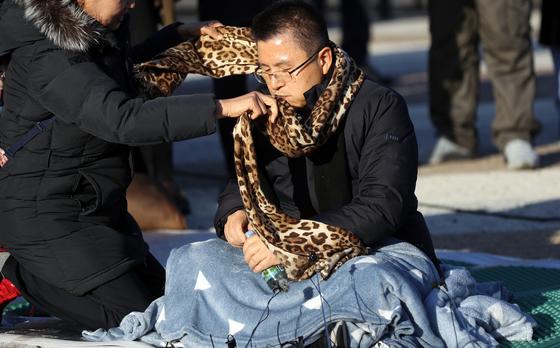20일 오후 청와대 앞에서 한 시민이 단식투쟁을 시작한 황교안 한국당 대표에게 목도리를 둘러주고 있다. [연합뉴스]