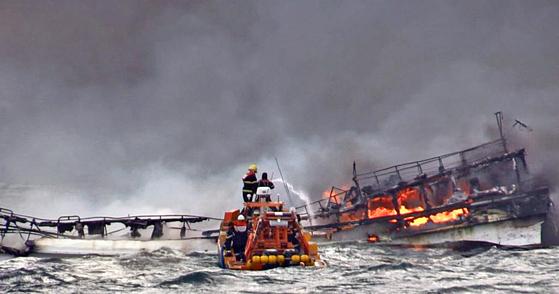 지난 19일 오전 제주 차귀도 서쪽 해상에서 12명을 태운 29t급 갈치잡이 어선에서 불이 나 해경 대원들이 진화 작업을 하고 있다. [연합뉴스]