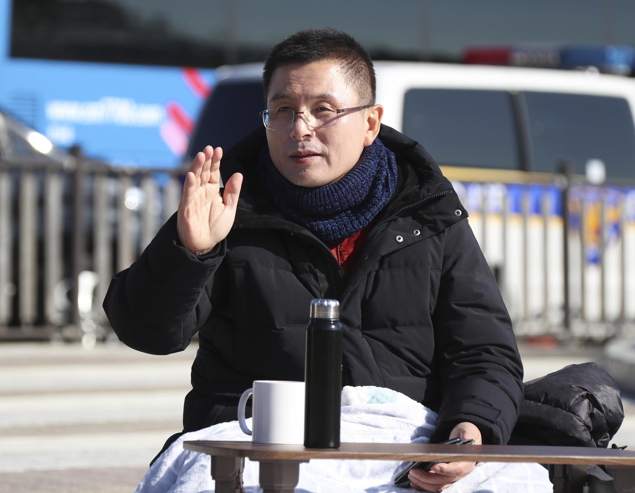 사흘째 단식농성 중인 황교안 자유한국당 대표가 23일 오전 청와대 앞 분수대 광장에서 지지자들에게 손을 들어 인사하고 있다.   임현동 기자