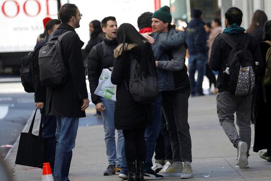 해고된 위워크 직원들이 미국 뉴욕 위워크 본사 앞에서 서로 껴안으며 얘기하고 있다. [로이터-연합]