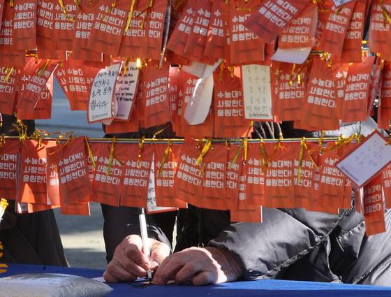 수능일인 14일 서울 종로구 조계사에서 신도들이 수능 대박을 기원하는 소원지를 적고 있다. [뉴스1]