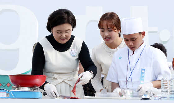 문재인 대통령의 부인 김정숙 여사가 22일 부산 전포동 놀이마루에서 열린 한-아세안 정상회의 D-3일 기념 음식 경연대회에서 캄보디아 팀과 요리를 하고 있다. [연합뉴스]
