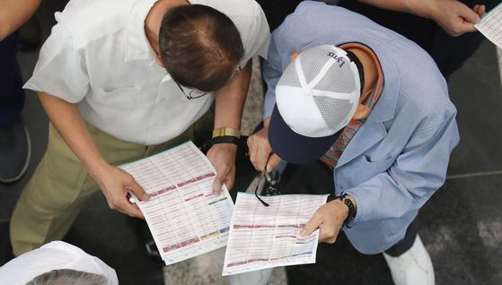 지난 9월 부산 해운대구 벡스코에서 열린 '60(60세 이상) 시니어 일자리 한마당'에 참가한 노인들이 채용 안내서를 살펴보고 있다. [중앙포토]