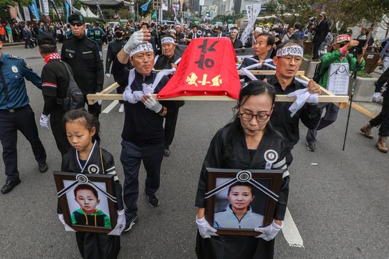 지난 9월 21일 오후 서울 광화문 교보문고 앞에서 열린 탈북모자 추모제 및 노제에서 탈북민 단체 관계자들이 모자의 영정과 상여를 들고 청와대 방향으로 행진하고 있다.  [뉴스1]