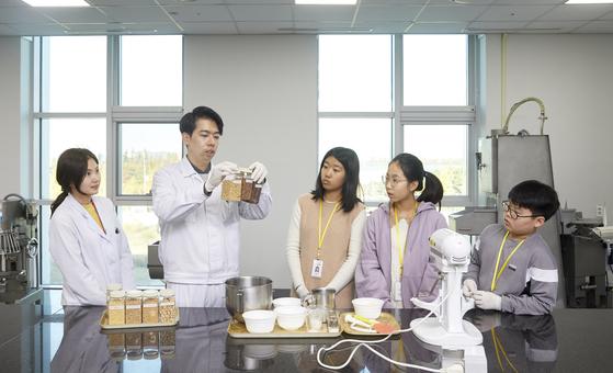 롯데중앙연구소를 찾은 소중 학생기자단이 식물성 고기의 원료 샘플을 살펴보고 있다. 왼쪽부터 박은지·안태경 연구원, 노효은·홍지수·허태훈 학생기자.