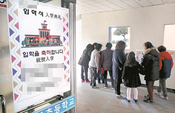 2017년 3월 서울 영등포구 대림동 A초등학교 입학식을 찾아온 부모와 학생. 안내문에 중국어가 병기돼 있다. [중앙포토]