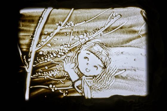 백서정 학생모델은 자신의 긴 생머리를 닮은 아이(위쪽 그림), 이은채 학생기자는 구불구불한 자신의 머리를 닮은 아이를 그렸다. 처음인데도 둘 다 근사한 샌드아트를 완성했다.