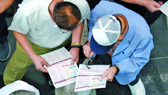 지난해 9월 부산 벡스코에서 열린 '60(60세 이상) 시니어 일자리 한마당'에 참가한 노인들이 채용 안내서를 살펴보고 있다. [중앙포토]
