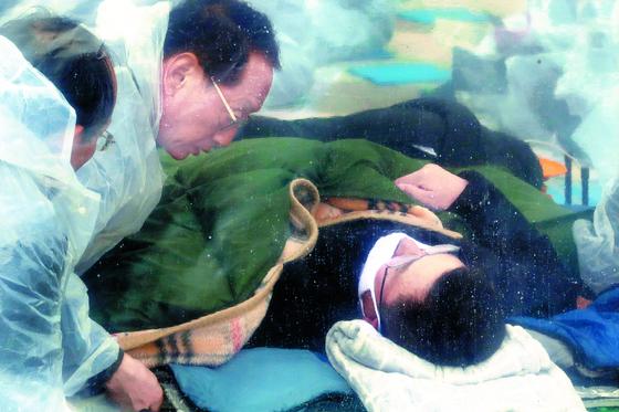 닷새째 단식농성 중인 황교안 자유한국당 대표가 24일 오후 청와대 분수대 광장에 마련된 텐트에 누워 있다. 왼쪽 둘째는 김도읍 비서실장.