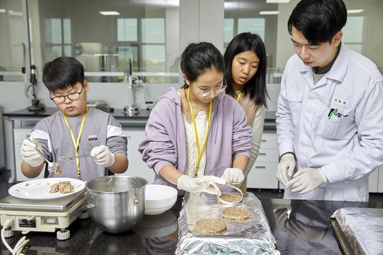 원료가 잘 배합된 반죽을 틀에 넣어 햄버거 패티 모양으로 만들고 있는 홍지수 학생기자.