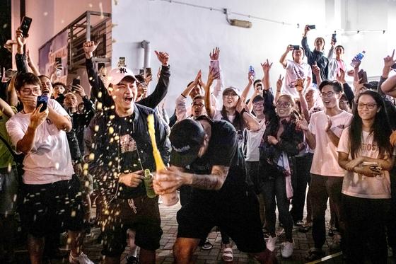 24일의 홍콩 구의원 선거의 개표가 진행된 25일 친중파가 줄줄이 낙선하고 범민주파가 당선하자 지지자들이 거리에서 샴페인을 터뜨리고 있다. 구의원 선거는 홍콩에서 이뤄지는 유일한 직접 선거다. [AFP=연합뉴스]