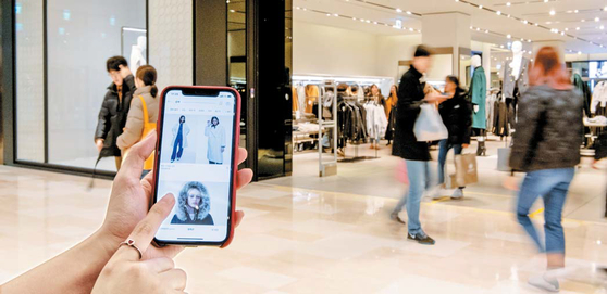 지난 15일 서울 신천동 쇼핑몰에서 직장인 여민지씨가 패션 매장에 들어서기 전 온라인몰에서 원하는 상품 수량을 확인하고 있다.