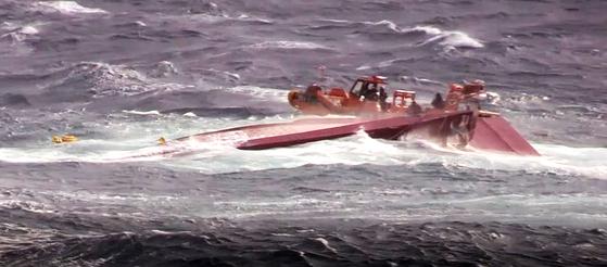 지난 25일 제주 마라도 남서쪽 해상에서 장어잡이 어선 창진호(24t)가 전복돼 제주해경이 사고 해역에서 승선원을 구조하고 있다. [뉴스1]