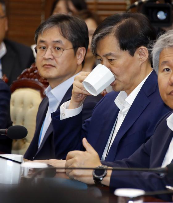 지난 5월 조국 당시 청와대 민정수석이 청와대에서 열린 수석보좌관회의에서 차를 마시며 목을 축이고 있다. 왼쪽은 박형철 반부패비서관. [연합뉴스]